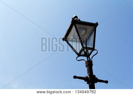 Old victorian lamp post against blue sky
