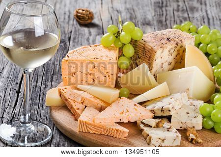 Cheese plate: organic homemade goat cheese with walnuts spices and glass of white wine. Green Grapes and walnuts on an old rustic background studio lights top view