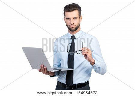 Confident business expert. Confident young handsome man in shirt and tie holding laptop and looking at camera while standing against white background