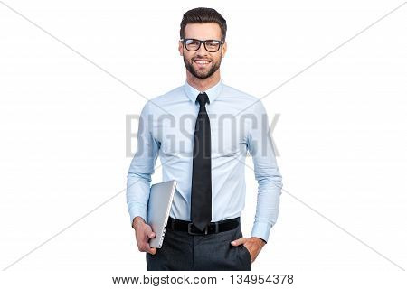 Confident businessman. Confident young handsome man in shirt and tie carrying laptop and looking at camera with smile while standing against white background