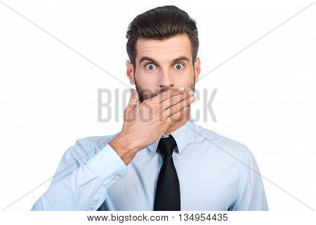 This is unbelievable! Surprised young handsome man in shirt and tie covering mouth with hand and staring at camera while standing against white background