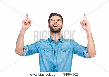 Just look at that! Happy young handsome man in jeans shirt pointing up and smiling while standing against white background
