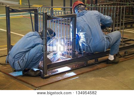 Welder working welding steel in the factory.