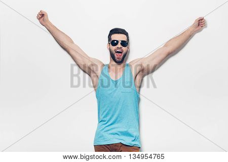Used to win every day. Confident young handsome man keeping arms raised and expressing positivity while standing against white background
