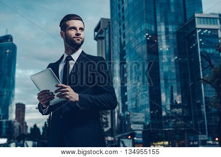 This is my city. Night time image of confident young man in full suit holding digital tablet and looking away while standing outdoors with cityscape in the background