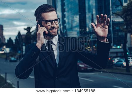 I can already see you! Night time image of confident young man in full suit talking on the mobile phone and waving to someone while standing outdoors with cityscape in the background