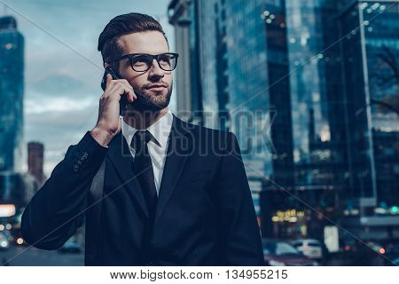 Business talk. Night time image of confident young man in full suit talking on the mobile phone and looking away while standing outdoors with cityscape in the background