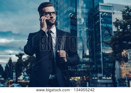 Business talk on the go. Night time image of confident young man in full suit talking on the mobile phone and looking away while standing outdoors with cityscape in the background