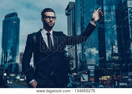 Catching taxi. Night time image of confident young businessman in full suit catching taxi while raising his arm and standing outdoors with cityscape in the background