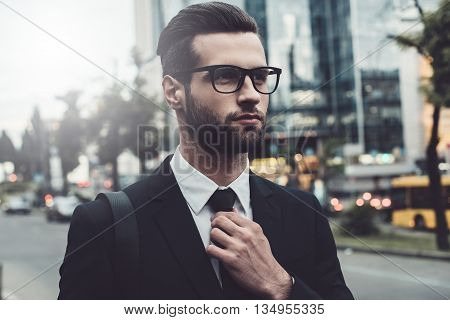 Making business look good. Confident young man in formalwear adjusting his necktie while standing outdoors with cityscape in the background