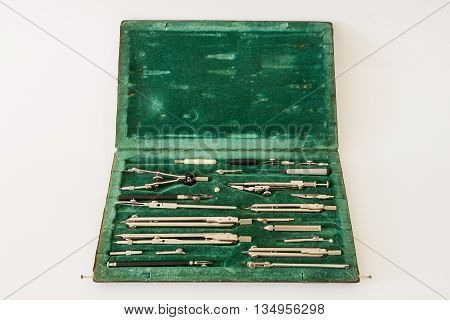 Vintage case of drawing instruments with compasses and other drawing implements on a worn green velvet.