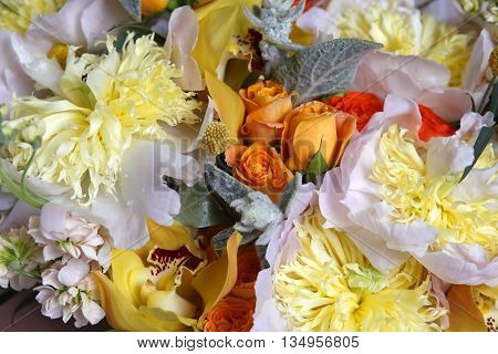 Wedding bouquet of roses orchids and peonies
