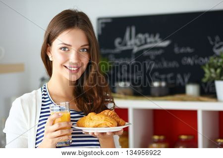 Young woman with glass of juice and cakes standing in kitchen .