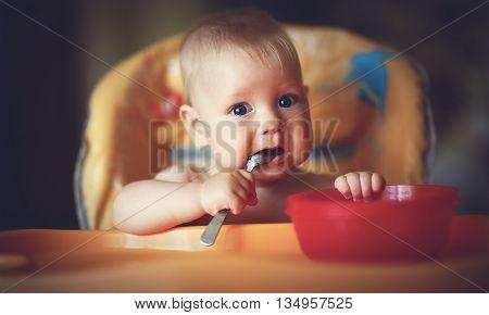 a Happy baby boy spoon eats itself
