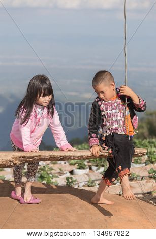 Chiangmai Thailand - December 7 2015: Countryside boy and girl in pink shirt playing wooden swing from hanging bench