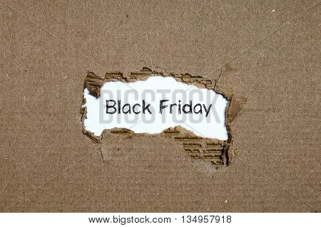 The word black friday appearing behind torn paper