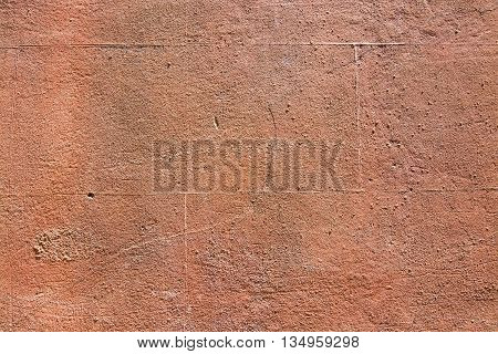 Red terra-cotta grungy roughcast horizontal background texture closeup.