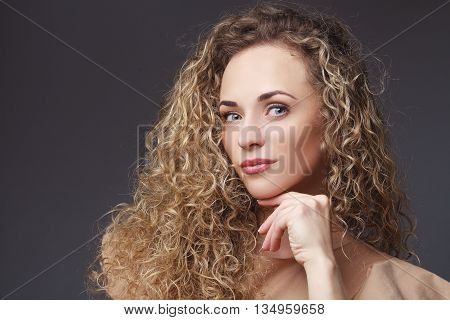 Beauty. Portrait of beautiful woman with curly hair thinking about something on black background in studio