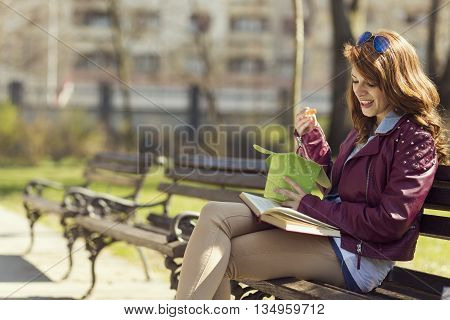 Young beautiful brunette sitting on a wooden bench in a park on a sunny day eating Chinese food
