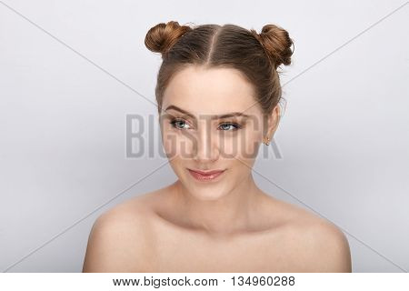 Portrait of a young woman with funny hairstyle and bare shoulders act the ape against white studio background
