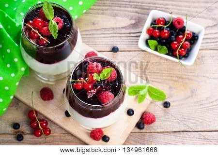 Healthy layered dessert with yougurt granola and jam on wooden background with space for text