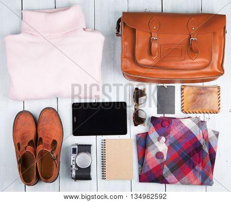 Tablet Pc, Clothes, Headphones, Camera, Shoes And Bag On The Desk