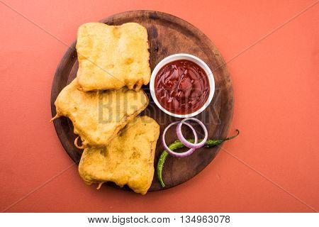 Bread Pakora or bread pakoda served along with tomato ketchup green chilly and onion slices, indian snack