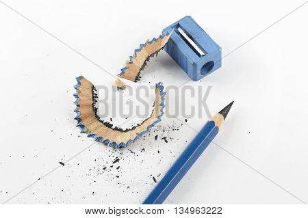 Close focus on sharpen blue pencil beside pencil sharpener and shavings on white paper