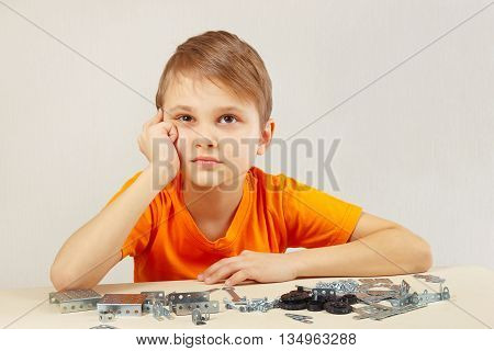 Little boy thinks that assemble from the mechanical constructor