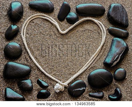 The concept of love. Black sea stones arranged around a frame heart shaped. Sandy background.