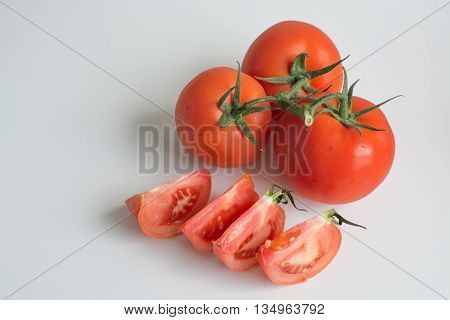 Several ripe truss variety tomato fruit isolated on white background with tomato slices