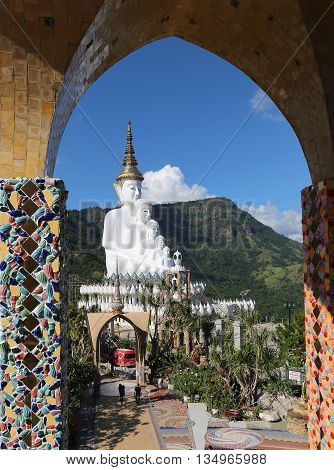 Phetchabun Thailand - November 23 2015: Seeing white buddha statue in Wat Phasornkaew or Glass cliff temple through dome decorated by colorful mosaic tiles.