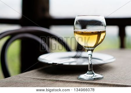 Wine glass and cutlery on the table. Closeup.