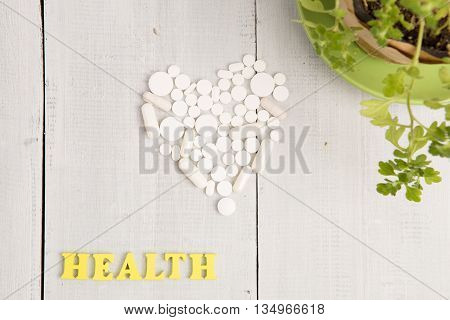 Medical Concept - Health  Inscription And White Heart Of Pills And Capsules