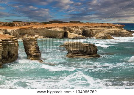 maritime landscape - turquoise sea with waves and rocks on background of dramatic cloudy sky. Cliffs at water. The Mediterranean coast near Paphos Cyprus