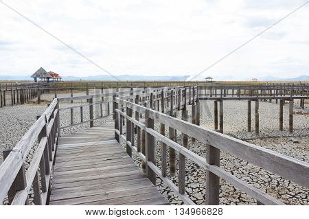 perspective wooden bridge with dry earth and cracked ground texture broken split land with soil background