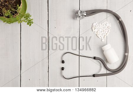 Medical Concept - Stethoscope, Bottle And White Heart Of Pills And Capsules