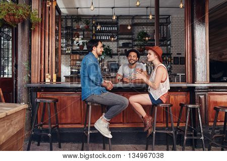 Portrait of happy group of young people meeting in a coffee shop and talking. Three young friends sitting at a cafe table.
