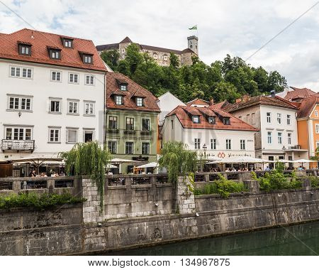 LJUBLJANA SLOVENIA - 26TH MAY 2016: A view along the Ljubljana River during the day. Ljubljana Castle buildings and people can be seen.