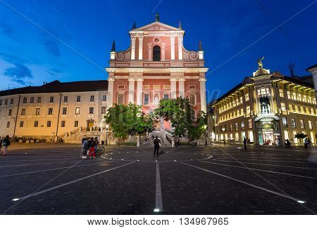 LJUBLJANA SLOVENIA - 26TH MAY 2016: The outside of Franciscan Church of the Annunciation and Preseren Square in Ljubljana at night. People can be seen.