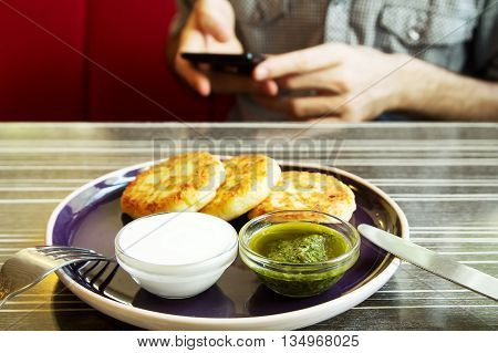 Homemade Salty Cheese Pancakes with sauce Pesto. Guy with the phone on the background. Pancakes photographed close.
