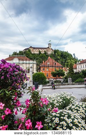 LJUBLJANA SLOVENIA - 26TH MAY 2016: A view towards Ljubljana Castle during the day. Flowers can be seen in the foreground