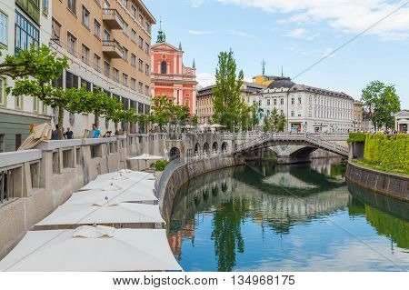 LJUBLJANA SLOVENIA - 26TH MAY 2016: A view along the Ljubljana canal towards the Franciscan Church of the Annunciation and Preseren Square. Other buildings and people can be seen.