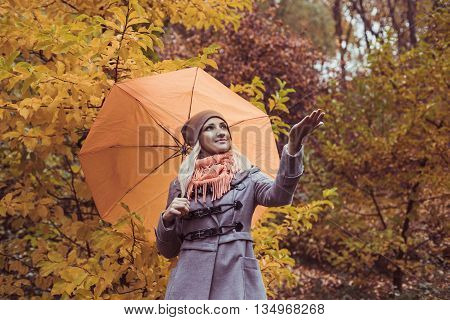 Pretty woman on backdrop of autumn leaves - seasonal relax concept