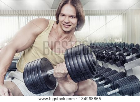 Close up strong man at the gym lifting weights