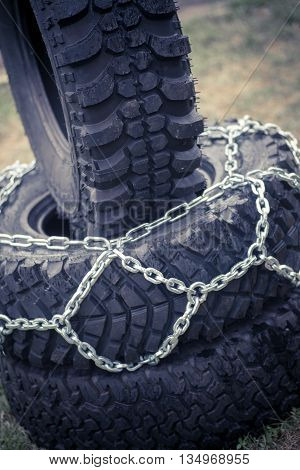 Close up shot of some chains wrapped around a car's tire.