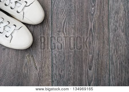 Nice pair of new white shoes on wooden desk