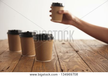 Three carton paper cups with black caps in row isolated on left side of rustic wooden table, woman hand takes another cup above