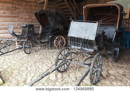 Empty Vintage Black Coaches Stand In Rural Garage