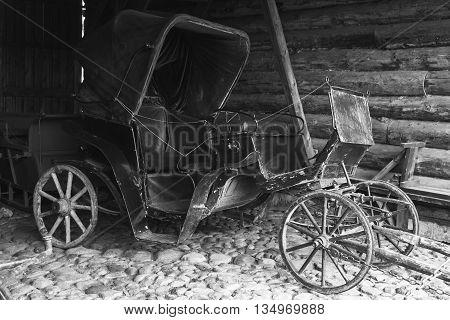 Empty Vintage Black Coach Stands In Rural Garage